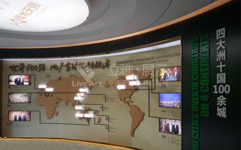 项目背景:佛山绿地中心·璀璨天城是集商务、商业、商旅、商贸、行政、文化、休闲、娱乐、居住等功能于一体的综合体,构建政务商务中心,金融商业中心,时尚消费中心,公共休闲中心与文化娱乐中心五大核心体系。 展厅设计制作特色1:前台背墙品牌墙底部为灯条,表面覆盖镂空不锈钢割样玫瑰金发光字,形象墙以两片15mm中纤板雕刻叠加喷漆做底,字体为拉丝不锈钢玫瑰金立体字,墙底垫脚(螺杆)离地10mm以构造弧形形象墙。继续往前深入参观,两侧墙面突出字体大都均以中纤烤漆板烤漆雕刻,地标及白色不突出字体则为丝印字体。